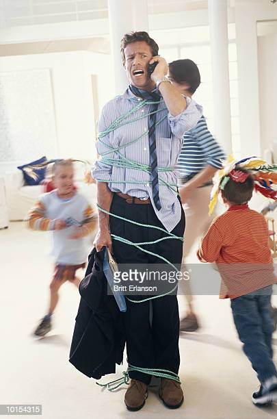 Children (4-7) tying up father with phone cord (blurred motion)