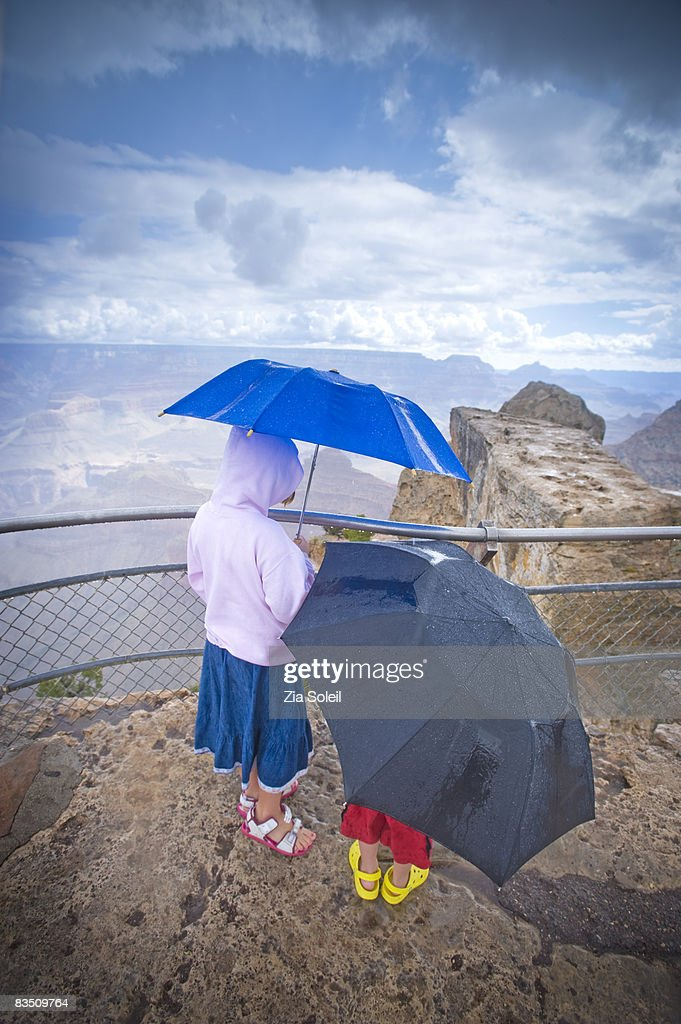 children under umbrellas at the Grand Canyon : Stock Photo