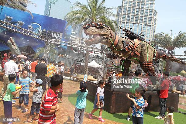 Children use a water pistol to take part in a dinosaur fight during the Songkran water festival The Songkran festival was sponsored by the Dinosaur...