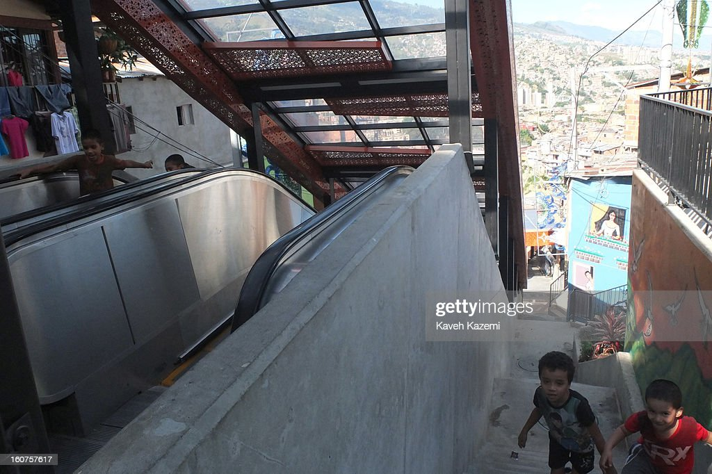 Children use the escalators in '20 de Julio' neighborhood in the Comuna 13 slums on January 5, 2013 in Medellin, Colombia. The stairway is divided into six sections and has a length of 1,260 feet. An escalator goes up and a second goes down.Residents used to climb hundreds of steps to get home from the bottom of the hill, but the journey now takes just 6 minutes. Comuna 13 is the most notorious slums of Medellin with violence occurring everyday.