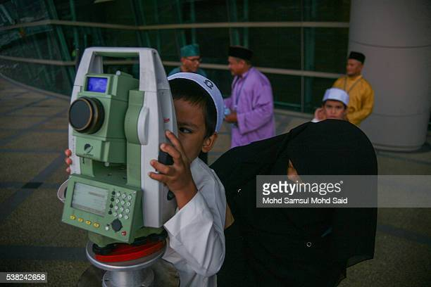 A children uses a telescope to perform 'rukyah' the sighting of the new moon of Ramadan in Putrajaya outside Kuala Lumpur on June 5 2016 Muslims scan...