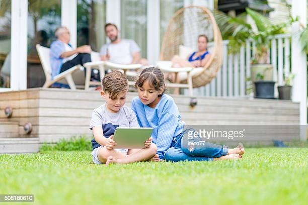 Crianças um utilizar um Tablet digital na relva