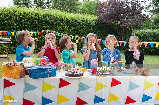 Children using party blowers on a birthday party
