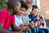 Pupils using mobile phone at the elementary school during recreation time. Group of multiethnic children sitting in a row and typing a message on smartphone. Young boys and girls playing with cellphon