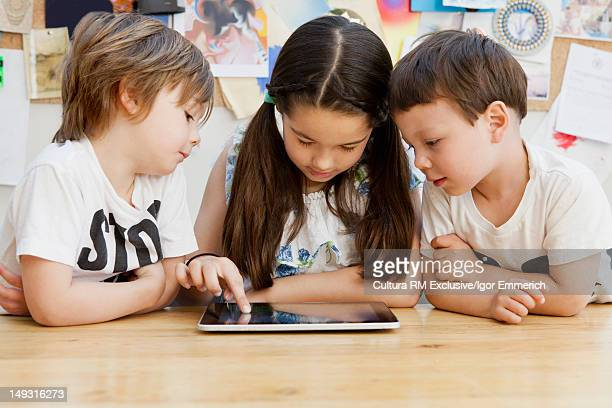 Children using tablet computer at table