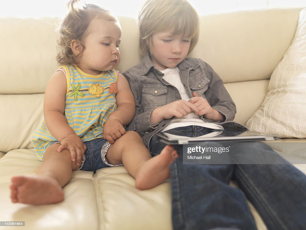 Children viewing tablet on couch : Stock Photo