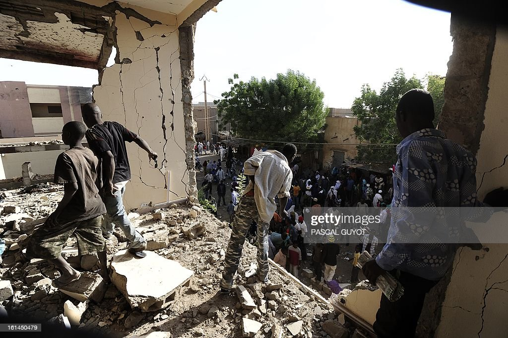 Children visit a damaged police station one day after Islamist gunmen battled French and Malian troops following two straight days of suicide bombings, on February 11, 2013 in Gao.