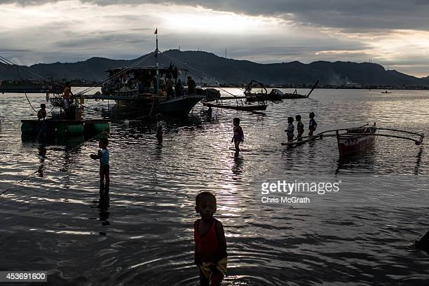 Children wade out to see fishing boats at the San Jose evacuation complex on August 16 2014 in Tacloban Leyte Philippines Many families are still...