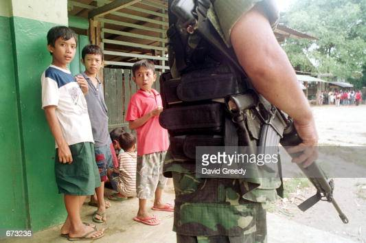 Children wait and watch under the safety of the Philippino army November 25 2001 at an evacuation center on the southern isle of Jolo Philippines...