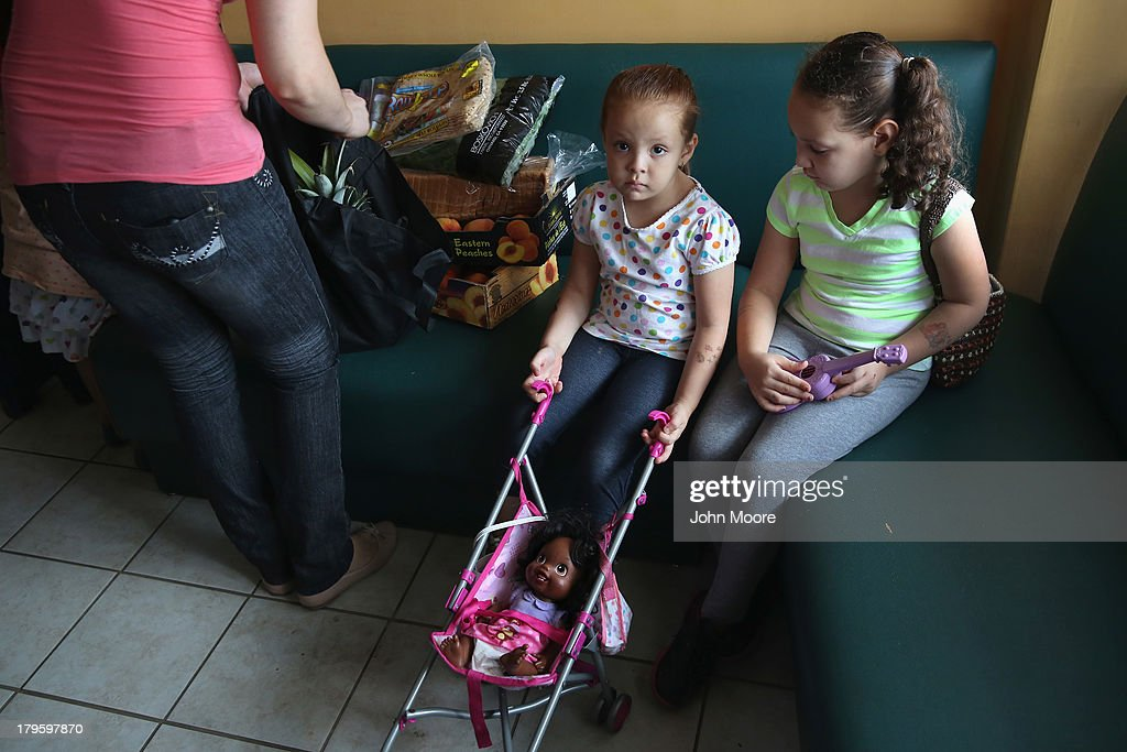 Children wait as their mother, an immigrant from Mexico, receives fresh produce at the New Americans Opportunity Center on September 5, 2013 in New Rochelle, New York. The immigrant center is part of the United Community Center of Westchester, which distributes fresh donated produce twice at week.