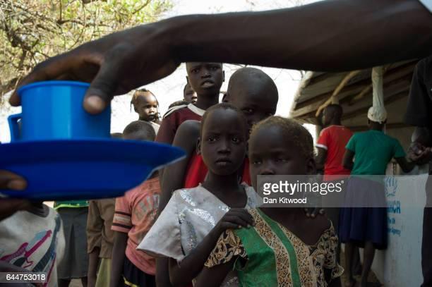 Children wait for cups of porridge as WFP The 'World Food Programme' prepare hot meals at the Imvepi Settlement on February 23 2017 in Imvepi Uganda...