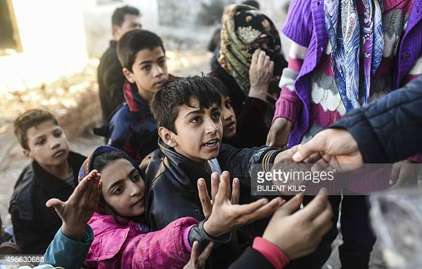 Children wait for food as they wait to go to the Greek island of Chios from Cesme in the Turkish province of Izmir on November 4 2015 Migrants have...