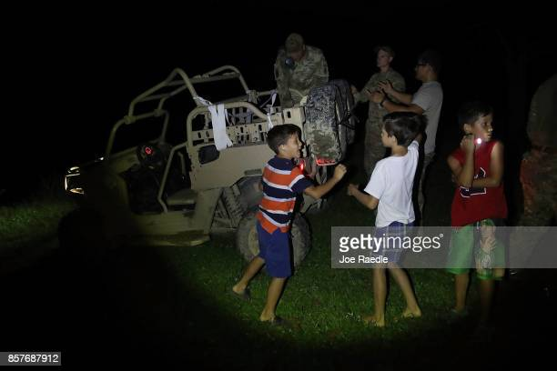 Children wait for members of the US Army 1st Special Forces Command to hand out water and food to people after Hurricane Maria swept through the...