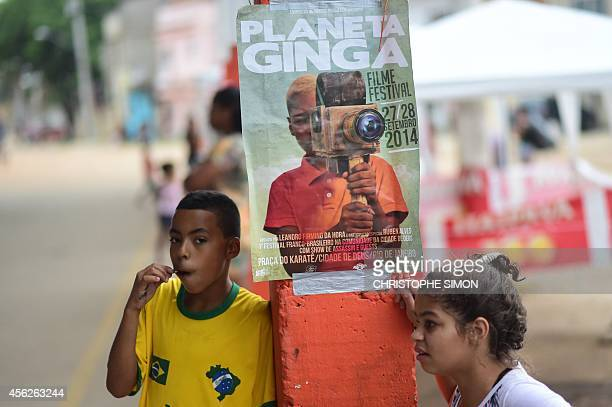 Children wait for the beginning of the BrazilianFrench 'Planeta Ginga' film and music free festival at the Cidade de Deus shantytown in Rio de...
