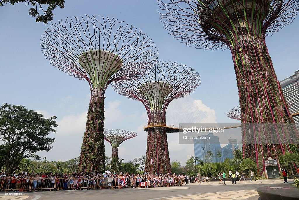 Children wait in the heat as Catherine Duchess of Cambridge and Prince William Duke of Cambridge visit the Gardens by the Bay on day 2 of Prince...