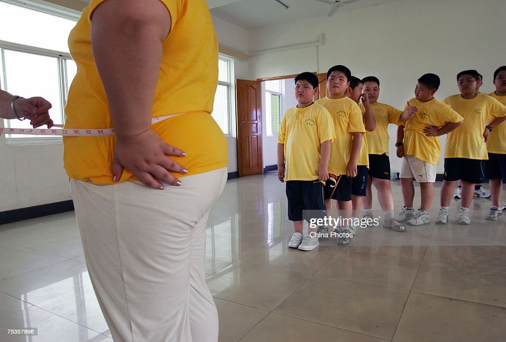 Children wait to be measured their waistline at a base of the Aimin Slimming Centre on July 10, 2007 in Wuhan of Hubei Province, China. Doctors in the center have combined acupuncture, exercise and diet to help about 110 obese teenagers from 9 to 20 years old lose weight during one month. An official from the Ministry of Health revealed that more than 200 million Chinese people are overweight.