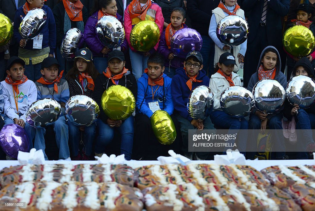 Children wait to get a piece of the traditional 'Rosca de Reyes' (Mexican Epiphany Bread) --a large ring-shaped bread roll baked for Epiphany-- in Mexico City, on January 3, 2012. The 1900-metre circumference 'Rosca de Reyes', weighing 10 metric tons --the world biggest-- was distributed among 200,000 people at Zocalo Square in the Mexican capital. AFP PHOTO/Alfredo ESTRELLA
