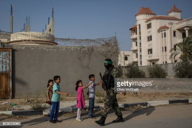 Children wait to shake hands as Palestinian Hamas militants pass by during a military show in the Bani Suheila district on July 20 2017 in Gaza City...