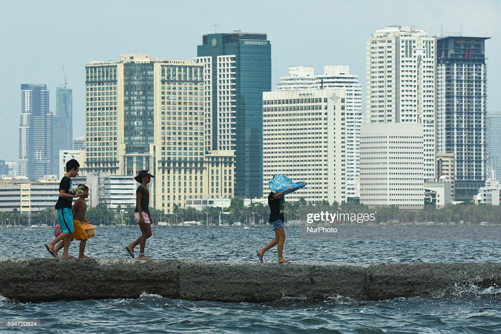 Children walk along a breakwater in a slum area in Tondo district Manila on 27 May 2016. Incoming Philippine president Rodrigo Duterte swore to invest on economic activity in the neighboring provinces of the countrys capital to reduce the overpopulated city of Manila overwhelmed by shantytowns.