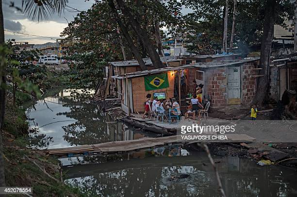 Children walk along a handmade bridge over a polluted stream as people watch the FIFA World Cup 2014 third place match between Brazil and the...