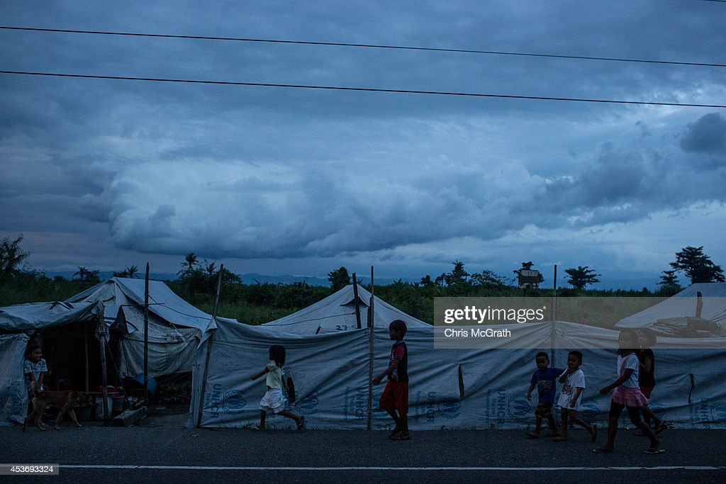 Children walk along the roadside back to their temporary tent homes at the San Jose evacuation complex on August 16, 2014 in Tacloban, Leyte, Philippines. Many families are still housed in temporary tent housing in the San Jose district. The families have been told that they will be rehoused before the visit of Pope Francis. Residents of Tacloban city and the surrounding areas continue to focus on rebuilding their lives nine months after Typhoon Haiyan struck the coast on November 8, 2013, leaving more than 6000 dead and many more homeless. With many businesses and government operations back up and running and with the recent start of the years typhoon season, permanent housing continues to be the main focus with many families still living in temporary accommodation. As well as continuing recovery efforts Leyte is preparing for the arrival of Pope Francis, who will visit the region from January 15- 19.