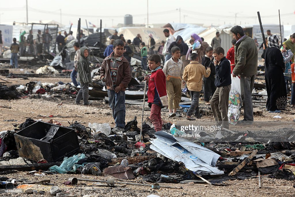 Children walk among the remains of a fire which broke out in Al Zaatari camp for Syrian refugees on March 8 2013 in Zaatari Jordan No refugees were...