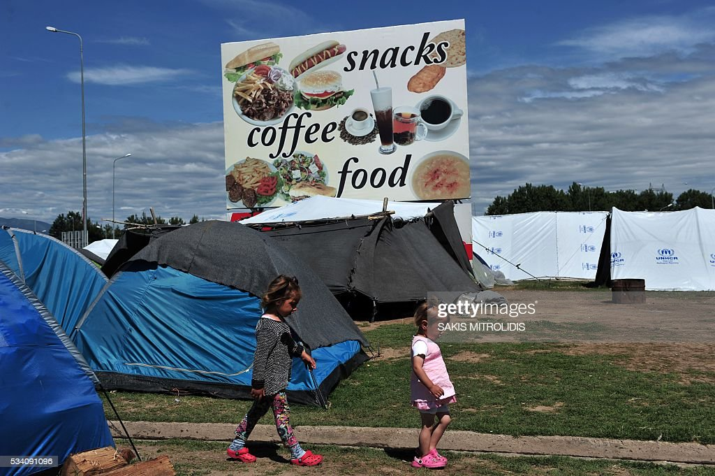 Children walk at a makeshift camp set near a gas station some 20 km from the Greek-Macedonian border, on 25 May, 2016 in Polykastro. In an operation which began shortly after sunrise on May 24, hundreds of Greek police began evacuating the sprawling camp which is currently home to 8,400 refugees and migrants, among them many families with children, an AFP correspondent said. At its height, there were more than 12,000 people crammed into the site, many of them fleeing war, persecution and poverty in the Middle East and Asia, with the camp exploding in size since Balkan states began closing their borders in mid February in a bid to stem the human tide seeking passage to northern Europe. / AFP / SAKIS