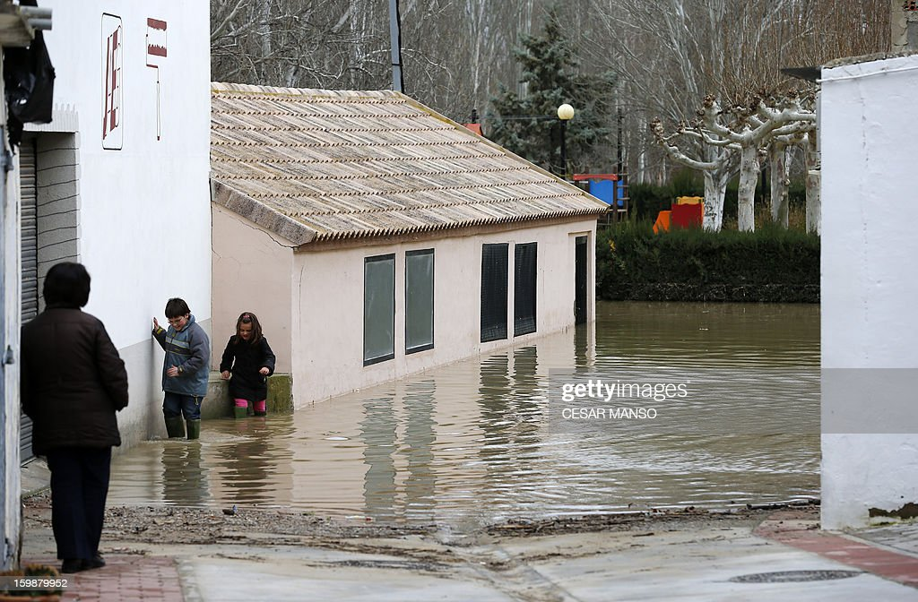 Children walk in a flooded street following the rise of the River Ebro, due to heavy rainfall, in Boquianeri, near Zaragoza, on January 22, 2013.