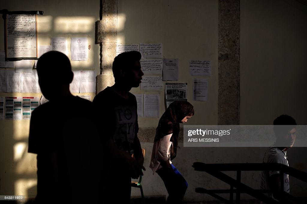 Children walk in an abandoned school used by volunteers for hosting families of refugeees from Syria and Afghanistan in Athens on June 27, 2016. / AFP / ARIS