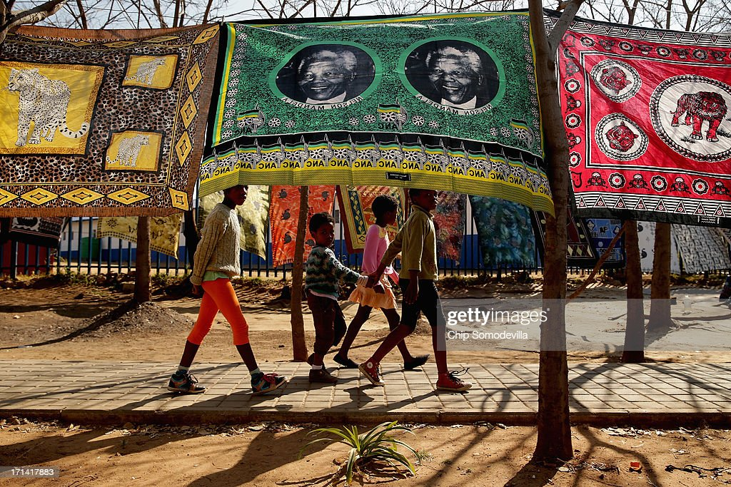 Children walk past souvenir flags picturing former South African President Nelson Mandela being sold across from the Hector Pieterson Memorial and Museum in Soweto Township June 24, 2013 in Johannesburg, South Africa. South African President Jacob Zuma confirmed that Mandela's condition has become critical since he was admitted to the hospital over two weeks ago for a recurring lung infection.