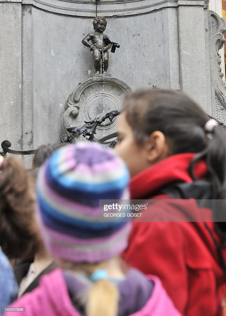 Children walk past the Belgian statue Manneken pis wearing a black arm band on March 16, 2012. Belgium observes a national day of mourning for the victims of the March 13 bus crash near the town of Sierre in southern Switzerland. Twenty-eight people died in the crash, including 22 children from two schools of Lommel and Heverlee, who were returning to Belgium from a skiing holiday. The first survivors of the accident returned to Belgium on March 16 . AFP PHOTO / GEORGES GOBET