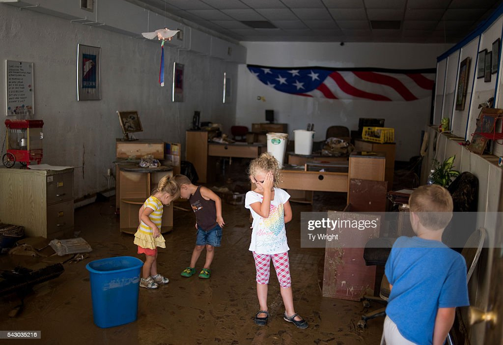 Children walk through a flooded Liberty Tax Service business on June 25, 2016 in Clendenin, West Virginia. The business was in operation for 16 years. The flooding of the Elk River claimed the lives of at least 23 people in West Virginia.