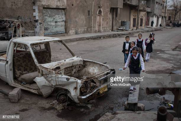 Children walk to school past destroyed cars in West Mosul on November 6 2017 in Mosul Iraq Five months after Mosul Iraq's secondlargest city was...