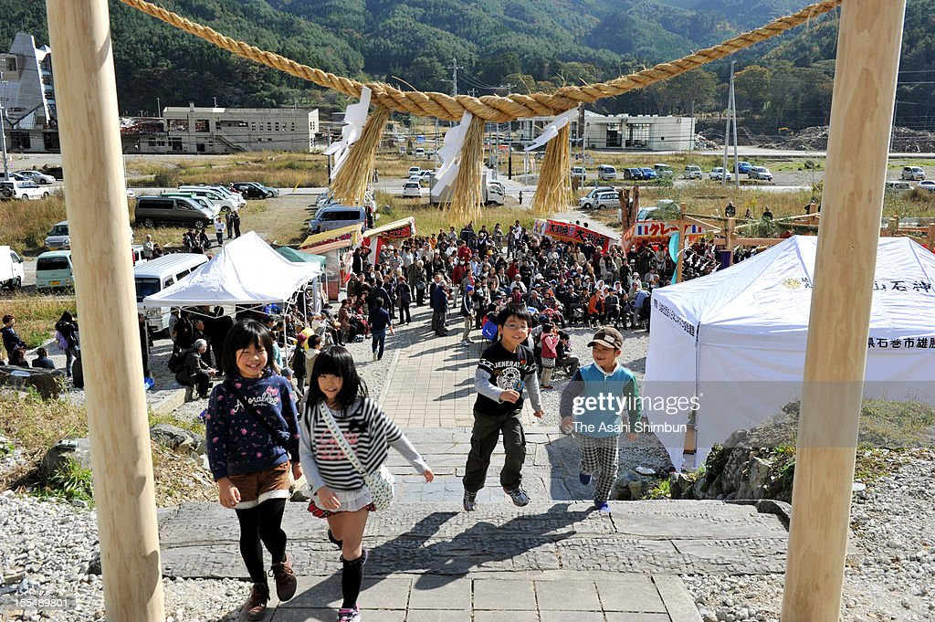 Children walk under the newly set shrine gate during the festival to celebrate the rebuilding of Niiyama Shrine on November 4, 2012 in Ishinomaki, Miyagi, Japan. This is the first shrine that Shrine Association support to rebuild, more than 200 shrines were destoryed by the last year's Great East Japan Earthquake and following tsunami, most of them are not afford to rebuild by theri own.