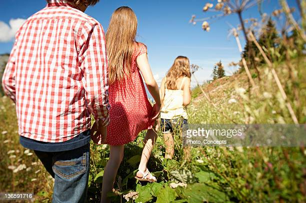 Children walking in tall grass