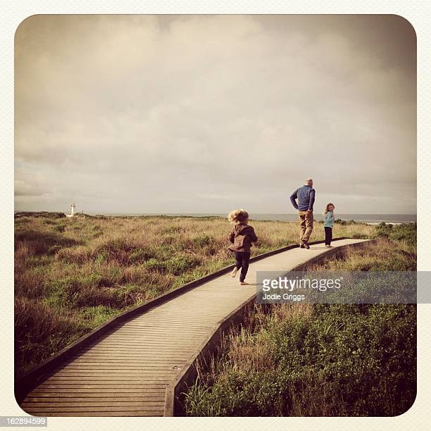 Children walking on coastal path with grandfather
