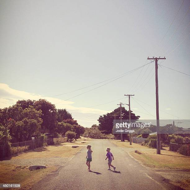 Children walking on road down quiet rural street