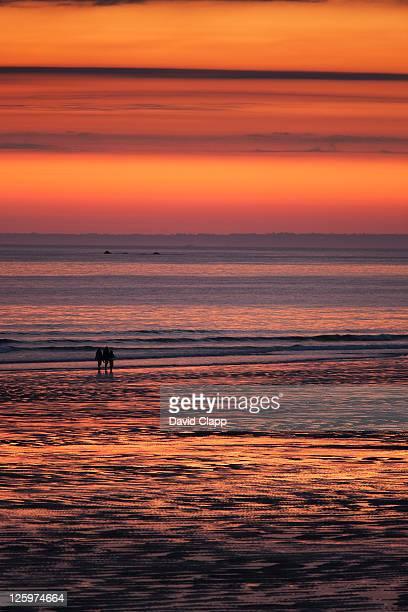 Children walking shoreline during sunset at St Ouen's Beach, Jersey, Channel Islands, United Kingdom