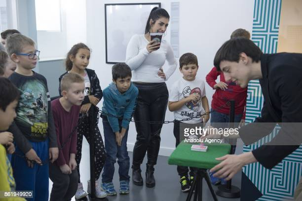 Children watch a card illusion at the Museum of Illusions in Vienna Austria on October 16 2017 The Museum of Illusions bring a collection of...