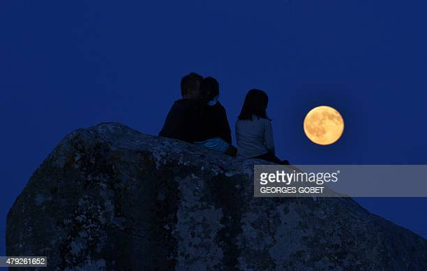 Children watch a full moon rising over the standing stones alignment of SainteBarbe in Plouharnel Brittany on July 2 2015 during the lunar...
