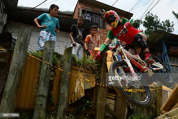 Children watch as a downhill rider competes during the Adrenalina Urban Bike race final at the Comuna 13 shantytown in Medellin Antioquia department...