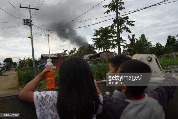Children watch as black smoke billows from burning houses after military helicopters struck the position of Islamist militants in a village on the...
