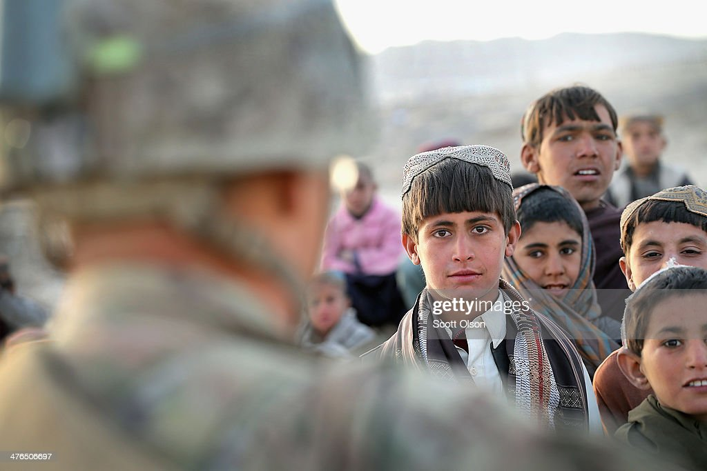 Children watch as soldiers with the U.S. Army's 4th squadron 2nd Cavalry Regiment patrol through their village on March 3, 2014 near Kandahar, Afghanistan. President Obama recently ordered the Pentagon to begin contingency planning for a pullout from Afghanistan by the end of 2014 if Afghanistan President Hamid Karzai or his successor refuses to sign the Bilateral Security Agreement.