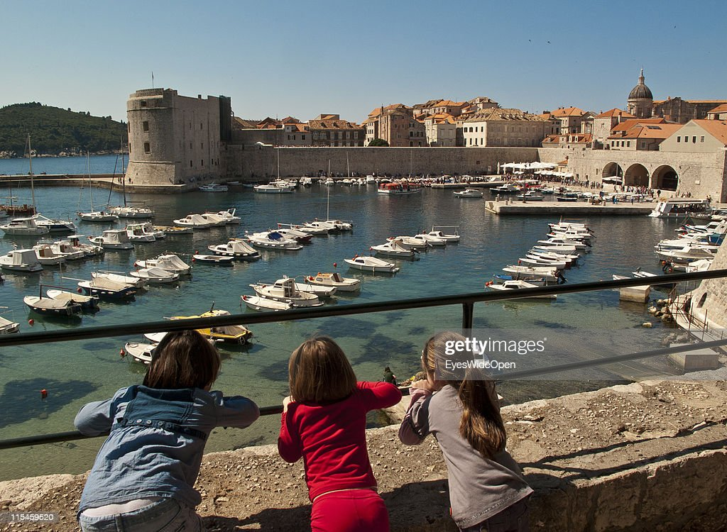 Children watch boats in old harbour port of walled city of Dubrovnik on Dalmatian coast of the Adriatic Sea on May 13, 2011 in Dubrovnik, Croatia. The old town of Dubrovnik is a UNESCO World Heritage Site and surrounded by a 1,9 km long city wall and called the Pearl of the Adriatic.