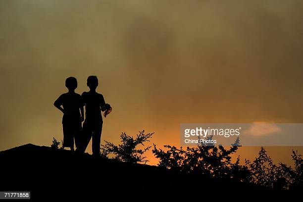 Children watch forest fires at Sansheng Township on September 1 2006 in Chongqing of Beibei District China The forest fires broke out on August 30 in...