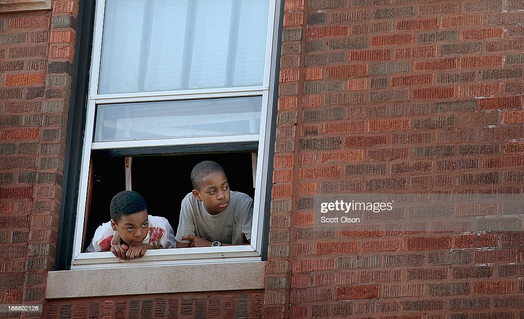 Children watch from a window of an apartment building as Chicago police investigate the scene of a shooting where two men were wounded in the South Shore neighborhood on May 14, 2013 in Chicago, Illinois. The shooting was the first of several that left two men dead and 11 others wounded in the city between Monday afternoon and the early hours of Tuesday morning.