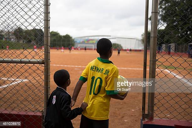 Children watch men play football on the 'Artur Alvim' club's dirt pitch in the poor neighbourhood of Itaquera adjacent to the 'Arena de Sao Paulo'...