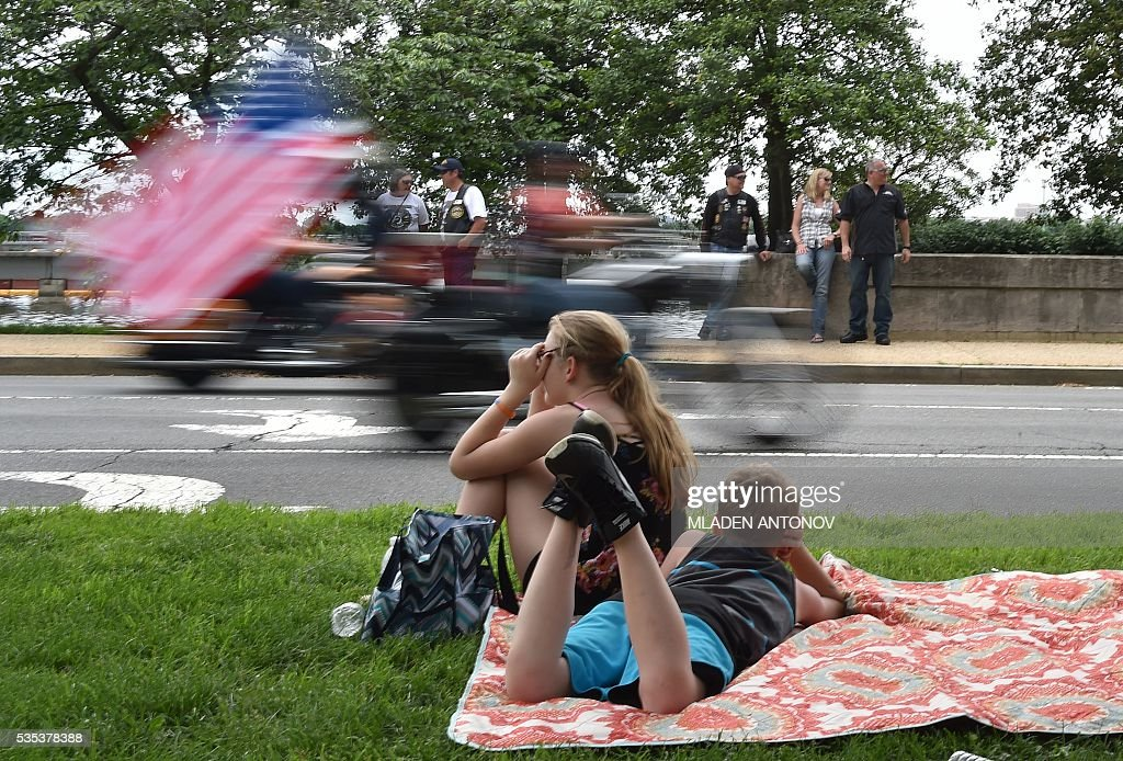 Children watch the annual Rolling Thunder 'Ride for Freedom' parade ahead of Memorial Day in Washington, DC, on May 29, 2016. / AFP / MLADEN