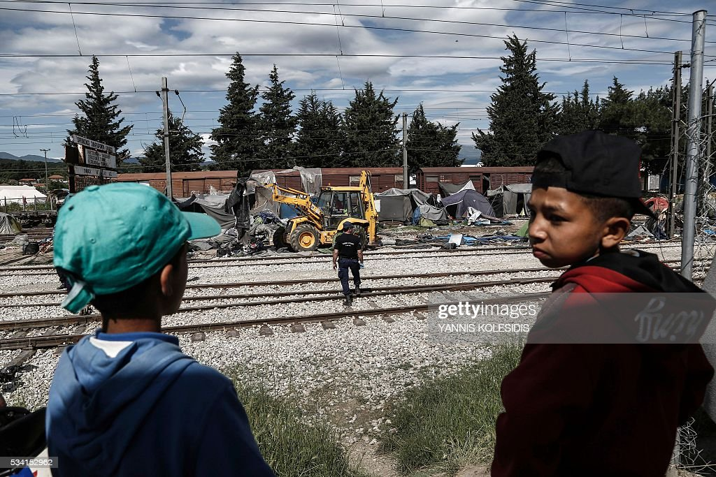 Children watch the police operation to clear the makeshift camp for refugees and migrants at the border between Greece and Macedonia near the village of Idomeni, northern Greece on May 25, 2016. Greek police restarted an operation to move migrants out of Idomeni, the squalid tent city where thousands fleeing war and poverty have lived for months. The migrants and refugees on May 24 were bussed to newly opened camps near Greece's second city Thessaloniki, about 80 kilometres (50 miles) to the south. / AFP / POOL / YANNIS