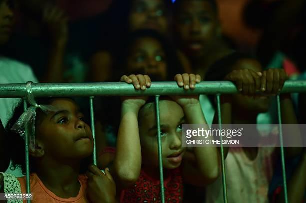 Children watch the show at the BrazilianFrench 'Planeta Ginga' film and music free festival at the Cidade de Deus shantytown in Rio de Janeiro Brazil...